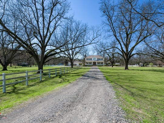 The long, winding drive leads up to 9820 Bayou Bend