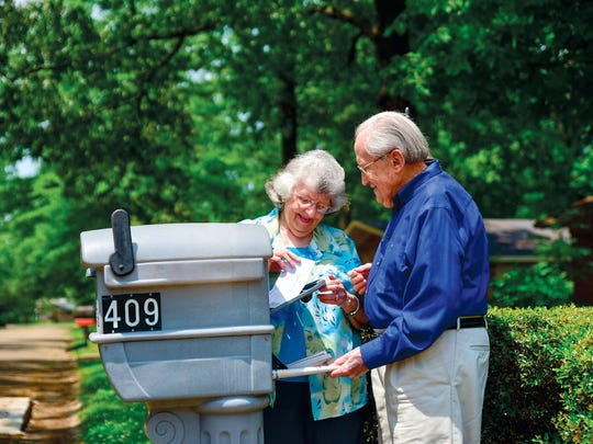 """In this May 9, 2018 photograph, retired carpenter and painting contractor Frank Gilliam and his wife, Edwina, both 84, get their mail and newspaper through the """"back doors"""" of their mailbox in Columbus, Miss. The double-door safety feature that keeps homeowners from having to step into the street to access mail was one Frank was building into mailboxes more than 20 years ago. """"I was tickled to see them,"""" he said about spotting double-door boxes years later in a Columbus home improvement store for the first time. """"I want folks to get those for their safety."""" Frank has compiled recommendations from his 70-year career in a guide titled """"Practical House Maintenance."""" (Luisa Porter/The Commercial Dispatch via AP)"""