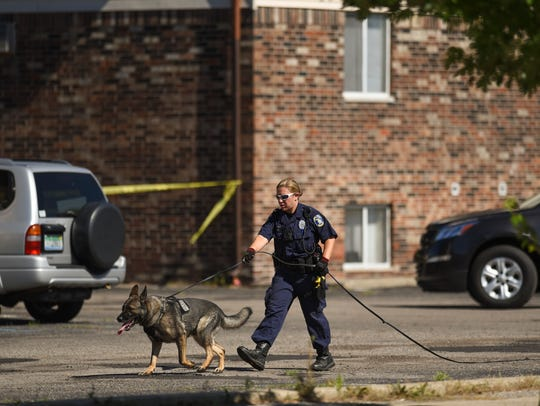 Members of the Lansing Police Department at the scene of a shooting in the 3200 block of Bardaville Street in Lansing.