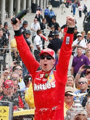 Kyle Busch celebrates after winning the Crown Royal 400 at Indianapolis Motor Speedway on Sunday, his third consecutive NASCAR Sprint Cup victory.