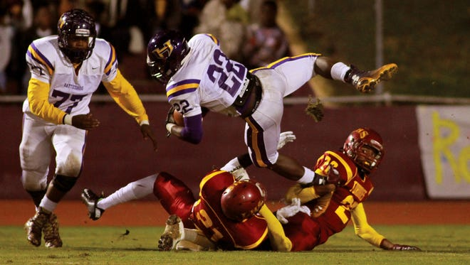 Hattiesburg running back Fabian Franklin (22) dives for a few extra yards over Laurel defenders Shiwon Lovett (20) and Daveon Rogers (21) during playoff action at Laurel.