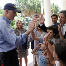 Florida Gov. Rick Scott, left, and Alberto Carvalho, superintendent of Miami-Dade County Public Schools, right, high-five school children before a news conference at the Southside Elementary School, Wednesday, Aug. 27, 2014, in Miami. Scott and Carvalho are asking the U.S. Department of Education not to hold Florida schools and teachers accountable for English language learners until after two years of instruction. Scott is running against former Republican Gov. Charlie Crist, who is running as a Democrat in November's election for Florida governor.  (AP Photo/Lynne Sladky)