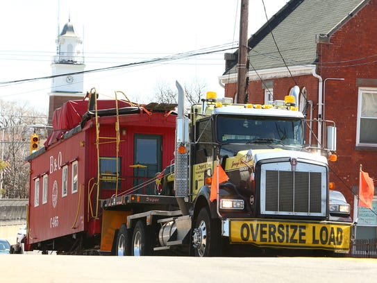 Historic 1922 B&O railroad caboose is pulled up Main