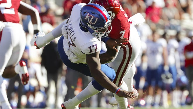 Kansas quarterback Jalon Daniels is sacked by Oklahoma's Ronnie Perkins during the first half of Saturday's game in Norman, Okla. Daniels was sacked nine times as the No. 19-ranked Sooners routed the Jayhawks, 62-9.