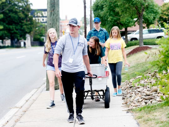 The group walks down Broadway led by Matthew Cook pulling the water wagon during the Win Our World (WOW) Urban Ministry program at St. John's Lutheran Church during a water handout along Broadway in Knoxville, Tennessee on Thursday, July 20, 2017. Because temperatures have been so hot, the youth provided water from a large pot to homeless in the mission district a couple of times this week.