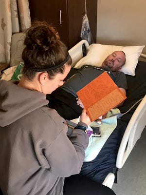 Sandy Hughes reads cards of support to her husband, Jeff, in the hospital after he was diagnosed with conversion disorder syndrome.