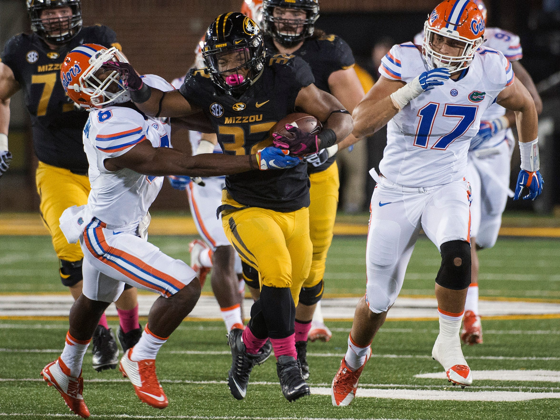 Missouri running back Russell Hansbrough, center, fights his way past Florida's Nick Washington, left, and Jordan Sherit, right, earlier this season. Some Missouri football players announced Saturday night that they will not participate in team activities until the university president, Tim Wolfe, is removed from office. The statement from the athletes of color was tweeted out Saturday by several members of the football team, including Hansbrough.