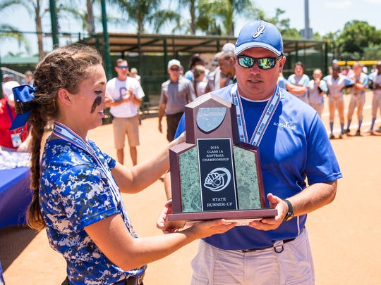 Jay High School's Miranda Roberts and coach Brian Watson accept the Class 1A state runner-up trophy after the 2015 Class 1A state softball championship game against Chiefland at Historic Dodgertown in Vero Beach.