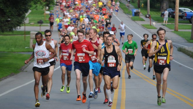 Runners sprint up Whitney Road in Fairport during the 2015 Firecracker Four Mile road race.