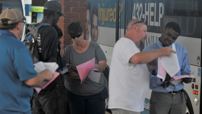 ECAT workers distribute flyers on Monday, June 6, 2017, to riders at the Rosa L. Parks Transit Complex in Pensacola.