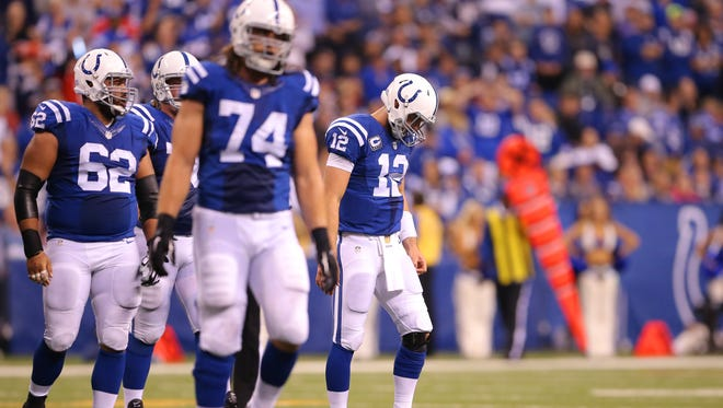 Andrew Luck (12), right, and the rest of the offense walk off the field after turning the ball over to New England after a failed fourth-down attempt, Oct. 18, 2015, at Lucas Oil Stadium.