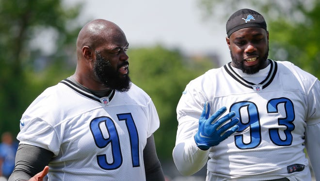 Detroit Lions defensive tackle Tyrunn Walker, right, talks with rookie A'Shawn Robinson after practice in Allen Park on May 26, 2016.