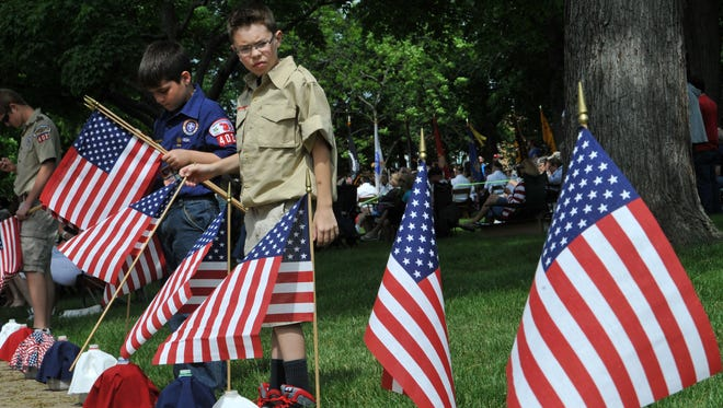 Cub Scout Lucas Casey looks back at the flags he has placed in remembrance of the veterans lost in the past year, Local Boy Scout and Cub Scout troops placed flags during the reading of names at the Memorial day services held on the court square.