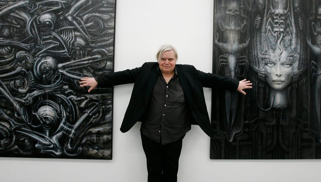 "Swiss artist H.R. Giger poses with two of his works at the art museum in Chur, Switzerland on June 29, 2007.  H.R. Giger, who designed the creature in Ridley Scott's sci-fi horror classic ""Alien,"" has died at age 74 from injuries suffered in a fall. Sandra Mivelaz, administrator of the H.R. Giger museum in Chateau St. Germain told The Associated Press Tuesday May 13, 2014  that Giger had died in a hospital the day before.  Giger  received a 1979 Academy Award for special effects in 'Alen'.  Giger's works, often showing macabre scenes of humans and machines fused into hellish hybrids, influenced a generation of movie directors and inspired an enduring fashion for ""biomechanical"" tattoos."