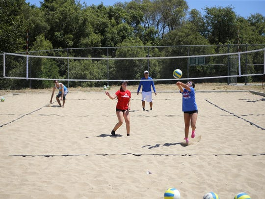 Coaches Korey Sawyer and Tyrone Toloy of the West Coast Volleyball Academy practice with players Shania Sitko and Briana Ayala on Friday afternoon at Natividad Creek Park in Salinas.