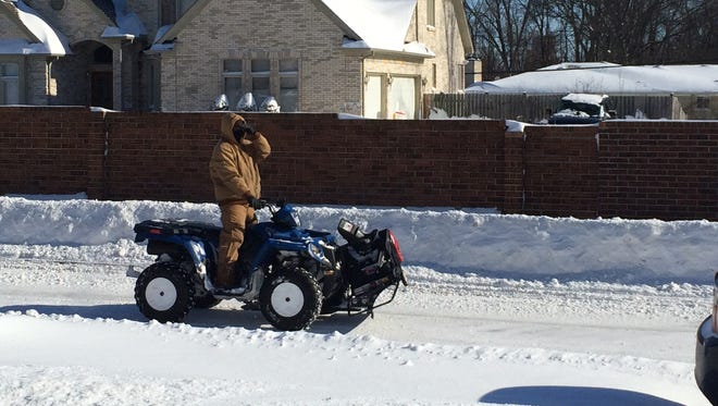 Bright sun Monday replaced swirling snow that measured more than a foot in Southfield as this ATV driver rides down a subdivision street in the 10 Mile and Telegraph area.