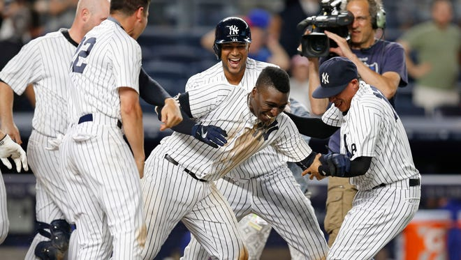Teammates celebrate with New York Yankees Didi Gregorius, center, after he hit a ninth-inning, walk-off, two-run, home run in the Yankees 9-7 victory over the Texas Rangers in a baseball game in New York, Wednesday, June 29, 2016.