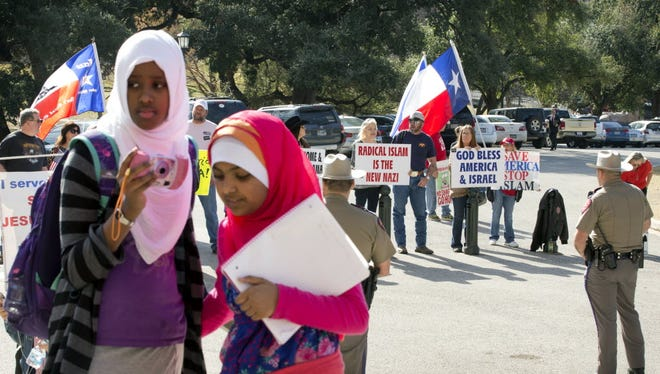 Amina Hassan, left, 11, of Grand Prairie, and Ayefa Klair, 10 of Irving, are faced with anti-Muslim protesters at the Texas Muslim Capitol Day in Austin, Texas, on Thursday, Jan. 29, 2015. Hundreds of Muslims from around Texas gathered for the Council on American-Islamic Relations rally and to talk to their representatives about legislation that's important to them.
