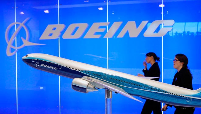 Boeing staff walk past a model plane on display at the Singapore Airshow in Singapore on Feb. 19, 2008.