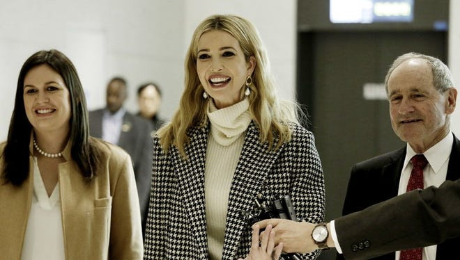 Flanked by White House Press Secretary Sarah Huckabee Sanders, left, Ivanka Trump, advisor to and daughter of U.S. President Donald Trump, speaks as she arrives at the Incheon International Airport in Incheon, South Korea, Friday, Feb. 23, 2018. Ivanka will lead her country's delegation to the closing ceremony of the Pyeongchang Winter Olympics Sunday.