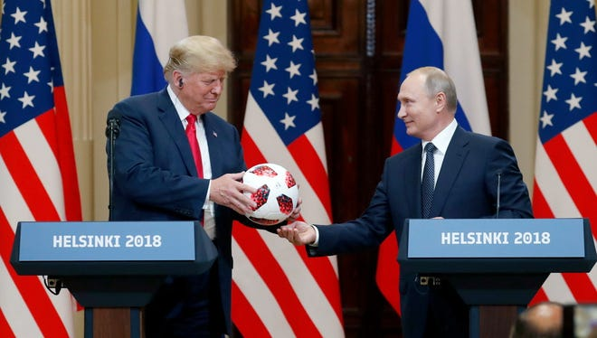 Vladimir Putin gives Donald Trump a soccer ball from the 2018 FIFA World Cup, Helsinki, Finland, 16 July 2018.