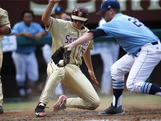 FSU's Cal Raleigh slides in safely at home plate under the glove of Rhode Island's Brad Applin during the third game of their series at Dick Howser Stadium on Sunday.