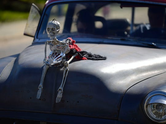A skeleton rests on the hood of a car Saturday during PensaCruise 2015 at Palafox Pier. PensaCruise 2015 features an all-day concert, parade of vehicles, food, bubble soccer and a bounce house.