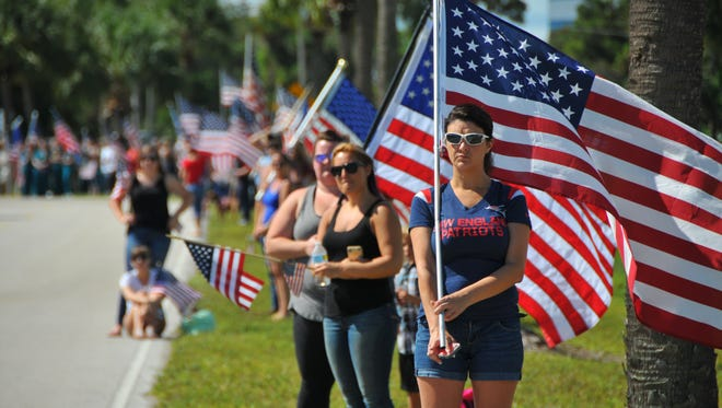Michelle Mandeville, of Melbourne, holds a flag to greet the remains of Army Sgt. Pablo Ruiz.
