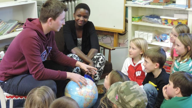 Dominik Gregora and Marie Nizigiyimana showing the Cabrini students where they live on the globe.