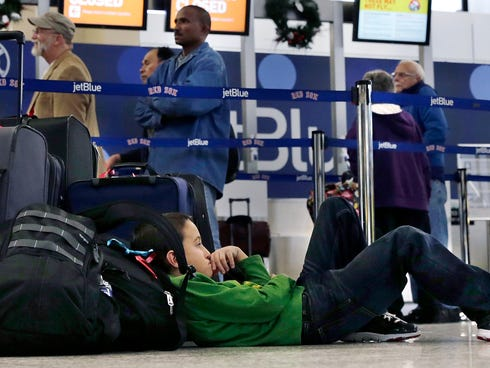 Seven-year-old Jordan Knowles rests his head against his family's luggage. They were rebooking their JetBlue flight back home to the Bahamas at Boston's Logan Airport on Monday, when JetBlue halted operations in Boston, New York and New Jersey due to