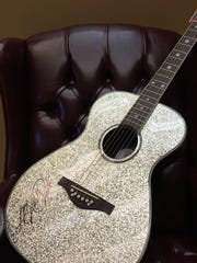 Dolly Parton donated this autographed guitar to auction to support families of the Chattanooga shooting victims.