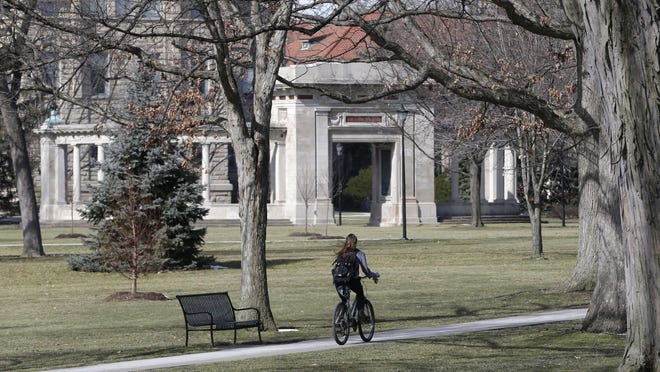 A student rides a bicycle on the campus of Oberlin College in Oberlin in 2013.