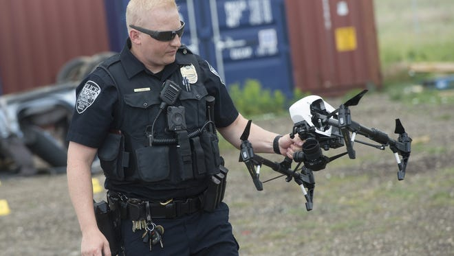 Colorado State University Police Officer Stephen Gurian carries a drone during a demonstration at the Poudre Fire Authority training facility on Thursday, June 22, 2017.
