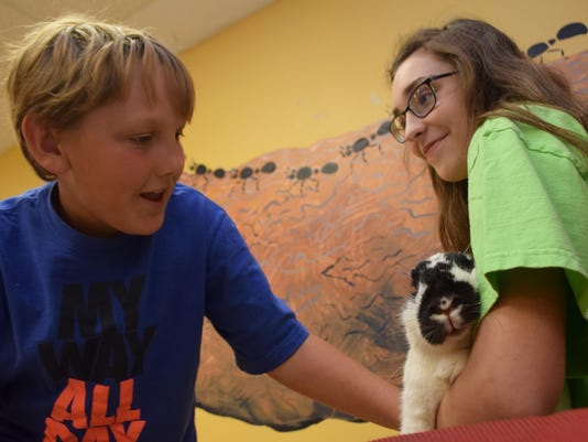 ANI TREEHouse Vet Gibson Russell, 9 (left), pets Cloudy, a rabbit belonging to Emily Backe (far right). Campers in the Get Set to Be A Vet Camp at the T.R.E.E. House Children's Museum are learning this week about how to care for animals.-Melinda Martinez/T