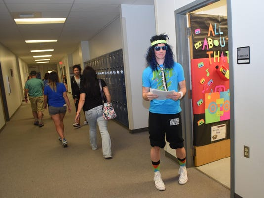 """ANI PHS '80s Night Pineville High School biology teacher Patrick Kelly dressed the part of a 1980s rocker to greet parents. Pineville High School held a parents' night with a """"Back to the Future""""/1980s theme. The purpose of the night was to welcome parents"""