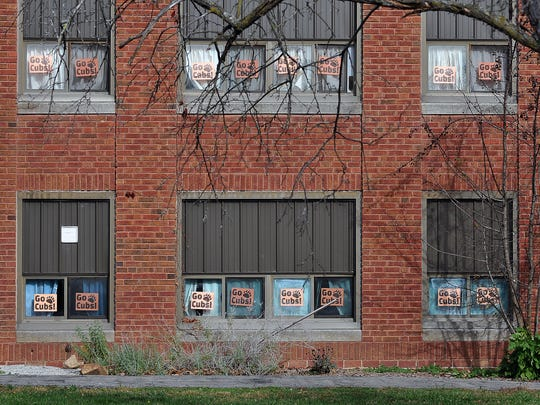 Signs supporting the football team adorn the windows of the high school in downtown Lucas Tuesday.