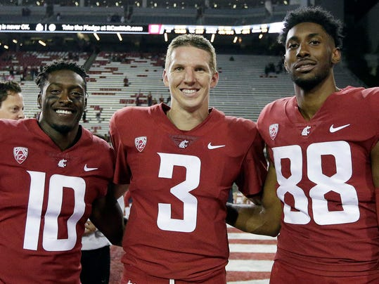 FILE - In this Sept. 9, 2017, file photo, Washington State defensive back Kirkland Parker (10), quarterback Tyler Hilinski (3) and wide receiver CJ Dimry (88) pose for a photo after an NCAA college football game against Boise State in Pullman, Wash. Hilinski has died from an apparent self-inflicted gunshot wound. The 21-year-old Hilinski was discovered in his apartment after he didn't show up for practice Tuesday, Jan. 16, 2018. (AP Photo/Young Kwak, File)