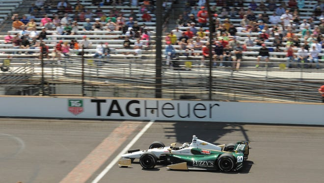 Pole winner Ed Carpenter drives past the new Tag Heuer decals at start/finish line at IMS.