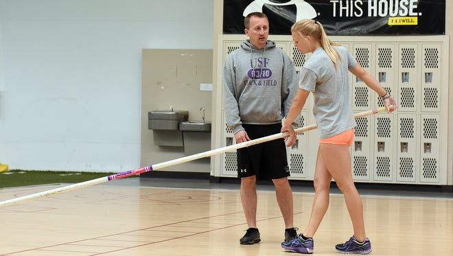 USF head coach, Reid Ehrisman, talks with Courtney Crandall about her form during pole vaulting practice at the USF complex in Sioux Falls, S.D., Tuesday, April 12, 2016.