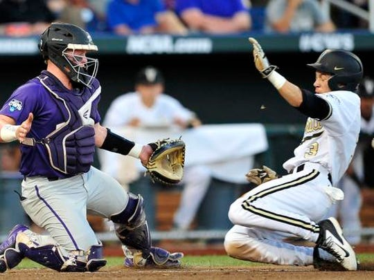 Vanderbilt's Jeren Kendall, right, beats a throw past TCU catcher Evan Skoug at home during the fifth inning in the College World Series at TD Ameritrade Park, Friday, June 19, 2015, in Omaha, Neb.
