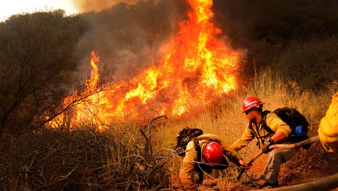 Firefighters run for their lives Saturday at De La Garrigue Road and Highway 150 near Ojai on Saturday. Crews were fighting the Thomas Fire, but the flames grew too big so they had to run. The blaze continued to burn strongly in that area on Saturday.