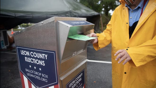In the middle of a heavy rain shower, Clark Brookstone, a volunteer poll worker, deposits a vote-by-mail ballot into a dropbox in the parking lot of the Leon County Supervisor of Elections Office Monday, August 17, 2020.
