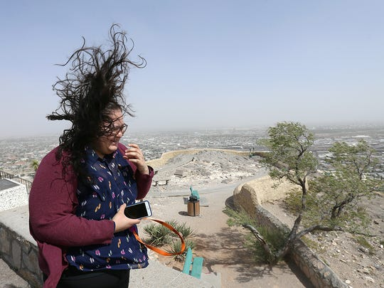 Andrea Perez braves high winds Thursday to look out