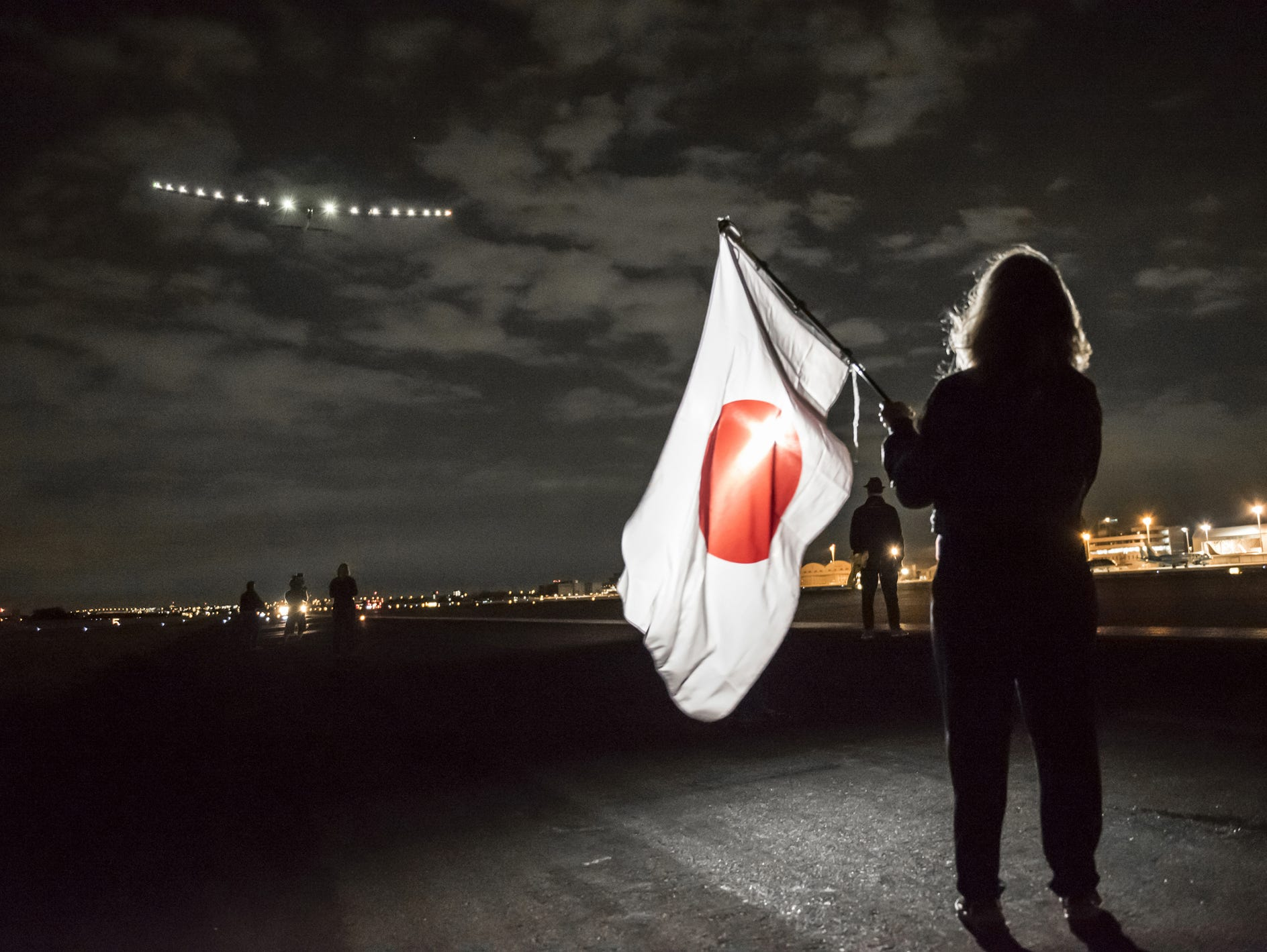 Yasemine Borschberg waves a Japanese flag as the Solar Impulse 2 takes off from the Nagoya Komaki airport with her husband Andre Borschberg as the pilot. The plane is en route to Hawaii after spending an unscheduled four-week stopover due to bad weat