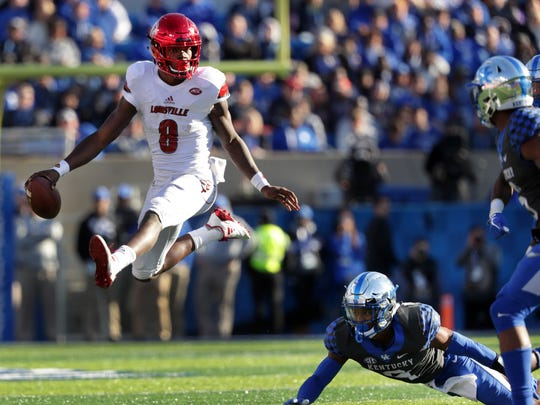 Louisville's Lamar Jackson hurdled two Kentucky players on his way to a long gain during second-half action. Nov. 25, 2017.
