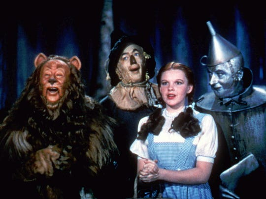"""Bert Lahr as the Cowardly Lion, Ray Bolger as the Scarecrow, Judy Garland as Dorothy, and Jack Haley as the Tin Woodman, sing in this scene from """"The Wizard of Oz."""""""