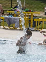 A youngster cools from the heat with a water feature at the Plymouth Aquatic Center.
