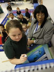 Davine Graves Wilson, a full-time substitute at Roosevelt-Perry Elementary School, works with kindergarten students as they learn their letters.February 16, 2017