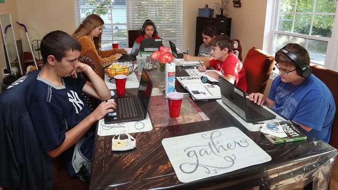 The Speck siblings -- from left, Zack, 16, Savannah, 17, Brooklynn, 15, Summer, 14, Aaron, 11, and Mitchell, 13 -- attend school online Sept. 4 at their dining room table in Norton.