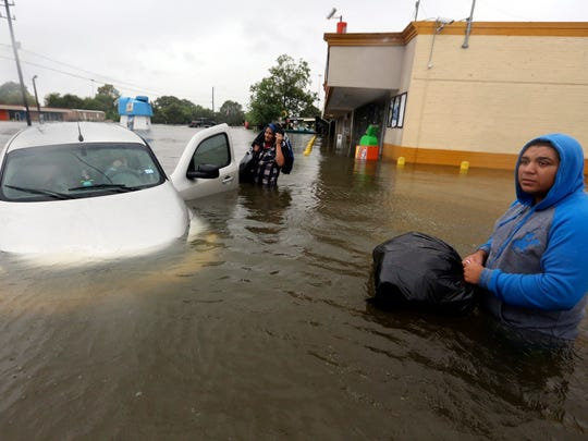Conception Casa, center, and his friend Jose Martinez, right, check on Rhonda Worthington after her car became stuck in rising floodwaters from Tropical Storm Harvey in Houston, Texas, on Aug. 28, 2017. The two men were evacuating their home that had become flooded when they encountered Worthington's car floating off the road.